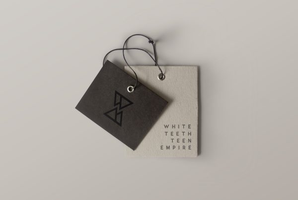 Picture of a clothes brand label in black and beige with white teeth teen empire logo